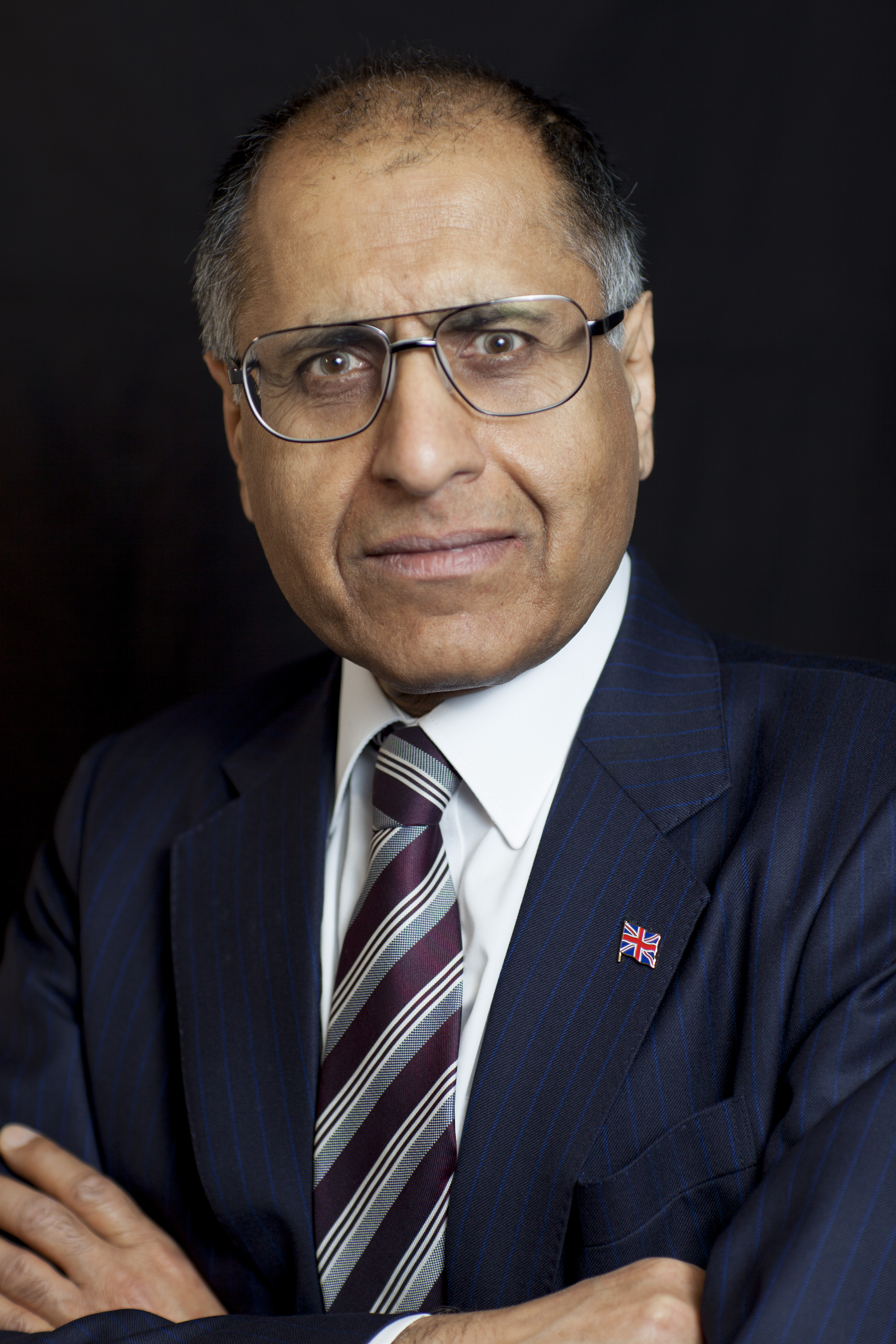 High resolution photo of Mohammed Amin wearing a jacket and tie.