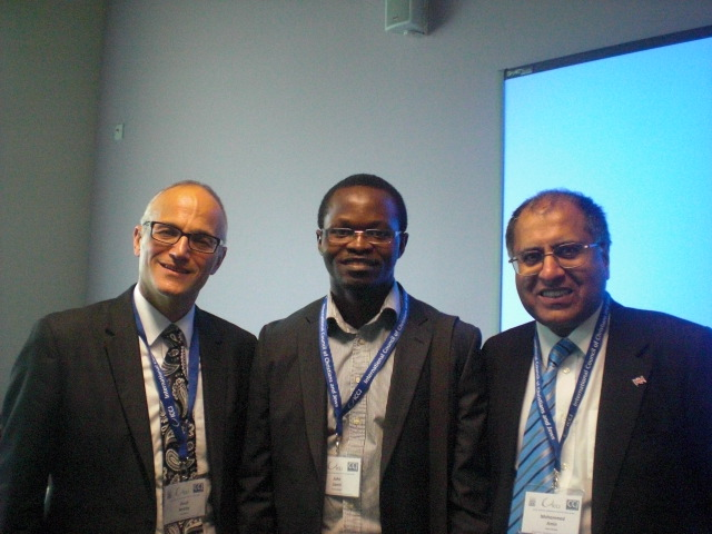 Photograph of David Berkley, Mohammed Amin and a conference participant